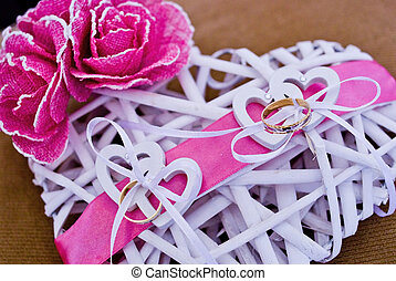 love rings of the newlyweds on heart decorated with pink bow