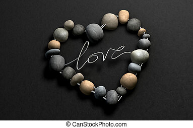 A handcrafted heart shape made out of wire and stones with the word Love spelt out on a stone background