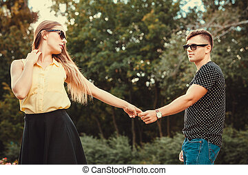 Cheerful girl holding hands in park.