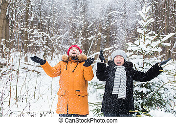 Love, season, friendship and people concept - happy young man and woman having fun and playing with snow in winter forest