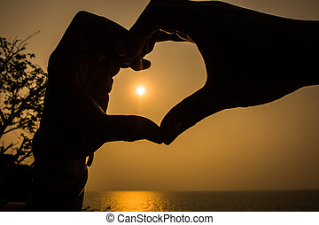 Love shape hand silhouette in the sky.