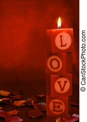 """Candles spelling out the word """"love"""" on a romantic background"""