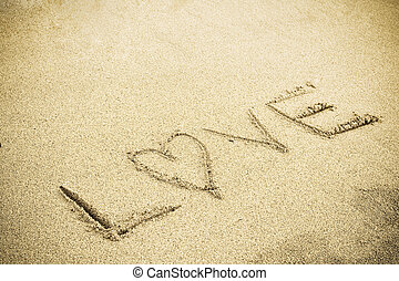 Love sign - A drawing of letter LOVE on the sandy beach