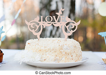"""""""LOVE"""" sign stuck into the cake"""