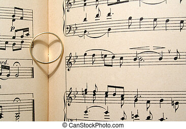 Golden wedding ring on old sheet music, casting a heart shaped shadow