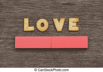 LOVE spelled out with Cookies on the top of a gray wooden board background