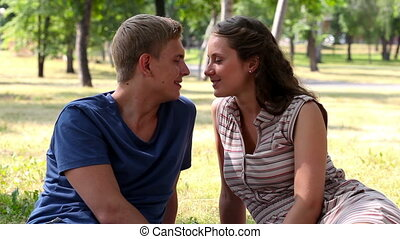 Love talk - Happy lovers talking and kissing outdoors on a...