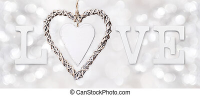 love text with heart of woven wood on silver blurred light background