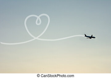 Love Travel Concept with Airplane Flying in the Sky Leaving Behind a Handmade Love Shaped Smoke Trail.