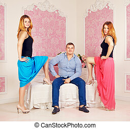 Love Triangle - happy man and two women in bedroom