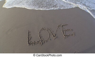Love Wash Away - The word love is written in the sand and a...