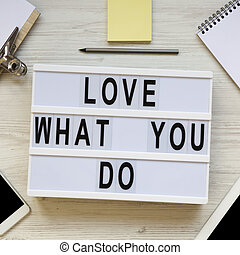 'Love what you do' words on lightbox, tablet, smartphone, notepad and pencil over white wooden surface, top view. Business concept. From above, flat lay, overhead.