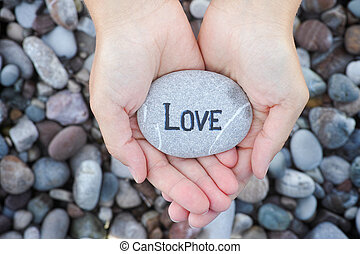 Woman holding stone with the word Love in her palms