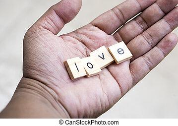 Love wooden blocks on Asian hand