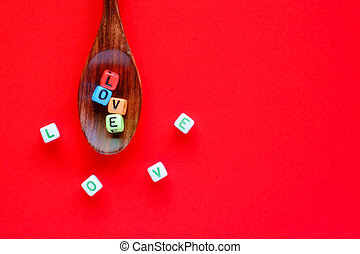LOVE word from alphabet letter bead on wooden spoon and spreading out on red background