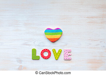 LOVE word in wood letters and rainbow heart shape pillow on wood vintage board. Valentines day concept. Mockup for LGBT.