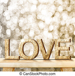 LOVE word in wood texture on wooden table with gold bokeh background, Valentine concept, Template that leave space for your content