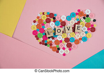 love word written on wooden block placed on colourful button in heart shape on colourful pastel background