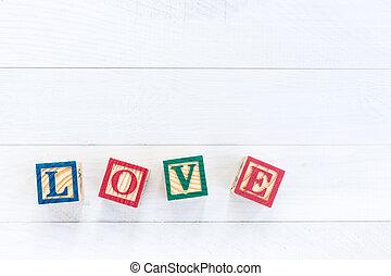 LOVE write in wooden alphabet block on white wooden background. Love concept or valentine day
