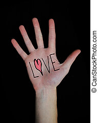 The word love written on a teenager's white Caucasian hand isolated on black background.