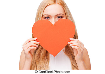 Love you! Beautiful young blond hair woman holding big heart shaped valentine card in front of her face while standing isolated on white