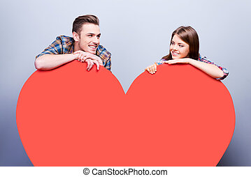 Love you! Beautiful young loving couple smiling and leaning...