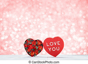 Love you word with Heart shape box with red roses inside on white wood table top at blur pastel pink sparkle bokeh light background, Love concept, Valentine's day card