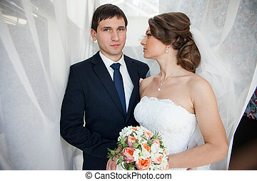 love young couple posing under the wedding veil