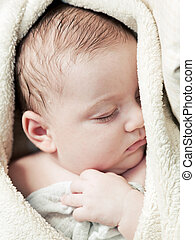 Lovely 3 months baby sleeping in soft blanket, close up face...