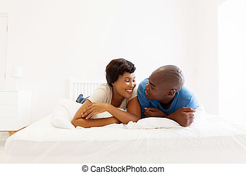 african american couple lying on bed