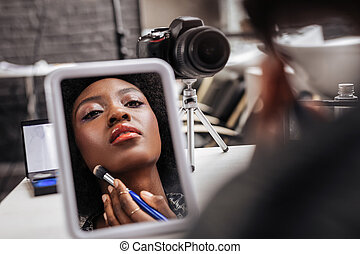 Lovely african american woman with coral lipstick looking busy