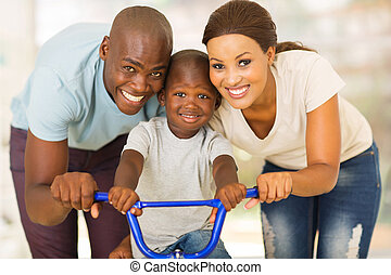 african couple teaching son to ride a bike