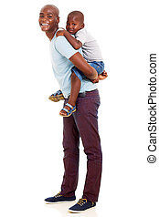 african father giving his son piggyback ride