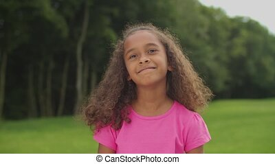 Portrait of lovely preadolescent african american girl with curly hair standing in summer nature, looking at camera with innocent radiant smile, expressing positivity, happiness and carefree mood.