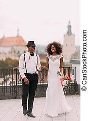 Lovely african wedding couple holding hands on the roof with...