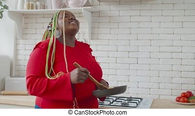 Lovely excited overweight african woman in casual clothes cooking, having fun and dancing with frypan and spatula while preparing food in domestic kitchen , expressing positivity and carefree mood.