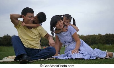 Lovely asian family with siblings relaxing at park