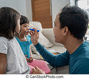 father paint his two daughter in the face