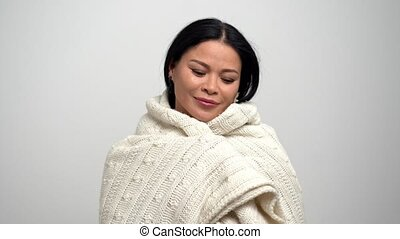 Lovely Asian woman getting warm wrapped in white scarf -...
