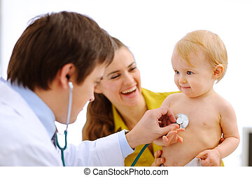 Lovely baby being checked by a doctor using a stethoscope