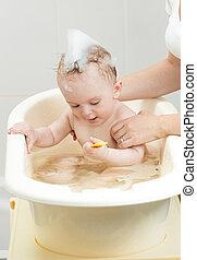 Lovely baby boy taking bath with foam
