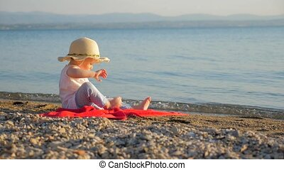 Lovely baby girl sitting on seashore. Little tourist sitting on red towel and looking on seascape. Summer time or recreations background. Family resort concept. Supportive environment. Autumn vacation