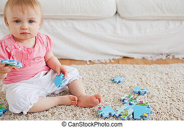 Lovely baby playing with puzzle pieces while sitting on a carpet in the living room