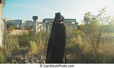 Lovely black sorceress with broom walking on ruins