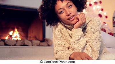 Lovely black woman in sweater and leggings lays seductively...