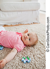 Lovely blond baby playing with puzzle pieces while lying on a carpet in the living room