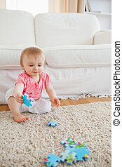 Lovely blond baby playing with puzzle pieces while sitting on a carpet in the living room