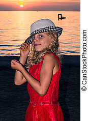 lovely blond child in hat in the beach