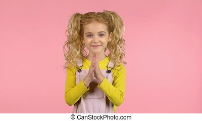 Lovely blond curly girl is clapping her hands