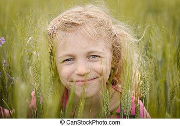 lovely blond girl portrait in green field